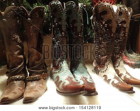 Studded brown leather cowboy boots on white sheepskin rug