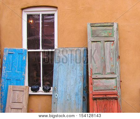 Carved painted and weathered doors leaning on a Santa Fe Style adobe wall.