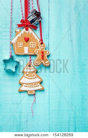 Gingerbread Man house and tree cookies hanging with ribbon over a blue background