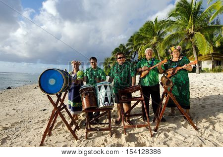 Group portrait of Polynesian Pacific Islanders band plays Tahitian music on tropical beach with palm trees in the background.