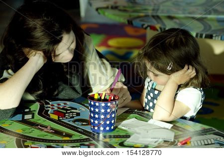 Young mother show her daughter how to draw and color a paint.