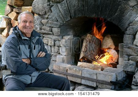 Mature Man Warm Up With Fireplace