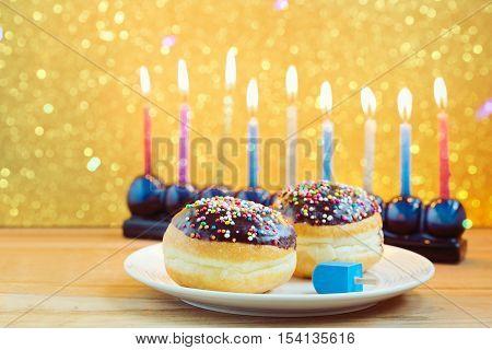 Hanukkah holiday sufganiyot with menorah on wooden table over bokeh background