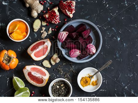 Ingredients for cooking beet and ginger detox elixir. On a dark background top view