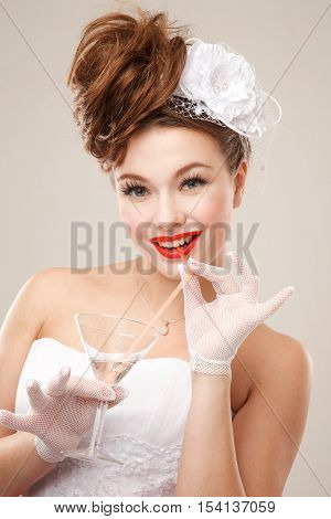 Pin-up bride drinks martini. Professional make-up hair and style