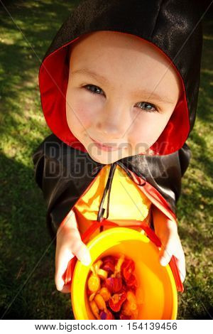 Boy in halloween costume trick or treating. Shooted with wide-angle lens effect