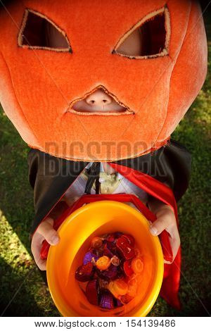 Boy in big pumpkin hat trick or treating.Shooted with wide-angle lens effect
