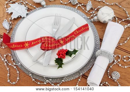 Christmas dinner table setting with porcelain plates, cutlery, linen serviette, red ribbon, silver and white bauble decorations with holly on oak background.