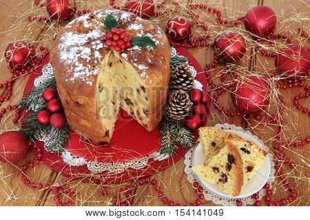 Italian panettone christmas cake and slice with holly berries, pine cones, red bauble decorations and gold tinsel strands over oak table background.