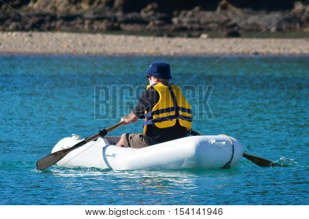 Man rows a rubber inflatable dinghy boat.