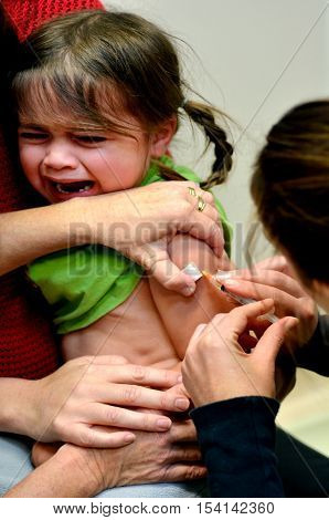 TAIPA, NEW ZEALAND - MAY 16 2014: A child (Talya Ben Ari age 4) receives an immunization of DPT and MMR vaccine New vaccines could avert nearly 4 million deaths of children under the age 5 by 2015.