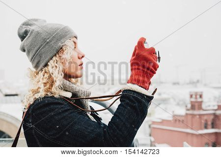 Young blond curly female in warm clothes with retro film camera shooting a photo from the roof on the background of winter city, snow