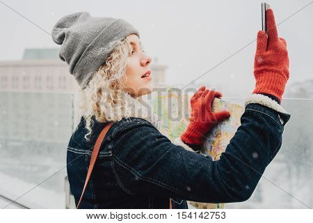Young blond curly female tourist in warm clothes and red gloves with London map making selfie or photo standing on the roof of winter city