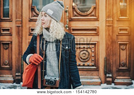 Young blond curly female tourist in warm clothes with red gloves and bag with retro film camera standing on the background of wooden doors winter