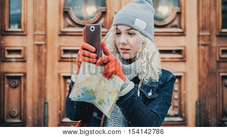 Young blond curly female tourist in warm clothes red gloves and map photographs or taking a selfie on smartphone, city street, winter, snow