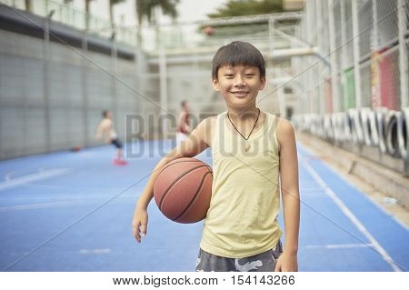Boy Standing Smiling At Camera With Basketball