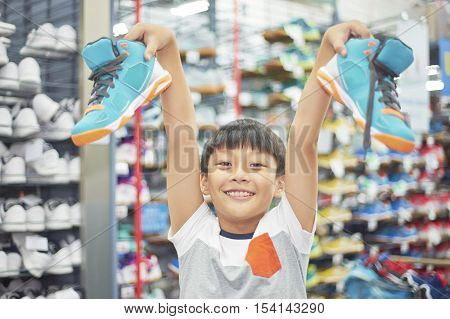 Boy Holding Chosen Shoes Smiling In Store