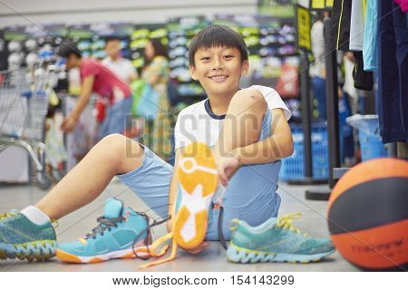 Boy Smilding Trying Sports Shoes In Shopping Mall