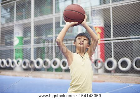 Boy Preparing For Shooting At Basketball Court