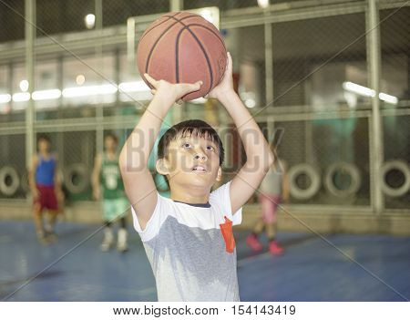 Boy Preparing For Basketball Shooting At Sports Field