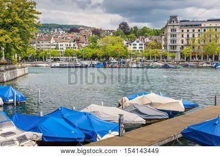Zurich Switzerland - May 24 2016: Architecture of Zurich the largest city in Switzerland and the capital of the canton of Zurich Switzerland. Boats in the foreground.