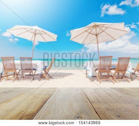 Wooden Table Top With Blur Of Table Set And Umbrella On The Beach