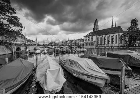 Zurich Switzerland - May 24 2016: Architecture of Zurich in overcast rainy weather the largest city in Switzerland and the capital of the canton of Zurich Switzerland. Boats in the foreground. Black and white photography dramatic sky.