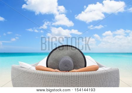Travel vacation woman relaxing lying down on sun bed sofa lounge chair on holidays. Sleeping person lounging in hat on outdoor beach daybed lounger on ocean background luxury vacation.