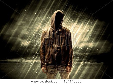 An incognito hooded stalker standing in the rain with his back in front of dark scary landscape concept