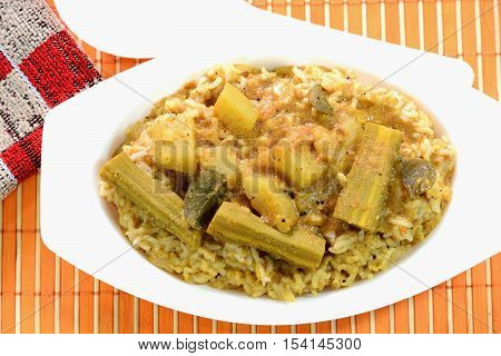 Bisi bele bhath is a rice based dish popular in the state of Karnataka, India. Prepared with rice, curry powder and vegetables.