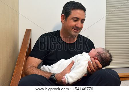 Happy father holds his newborn baby few minutes after childbirth.