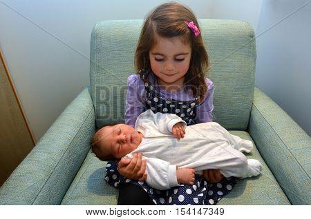 Happy little girl holds her newborn baby sister.