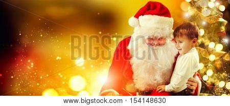 Santa Claus and Little Boy. Christmas Scene. Boy Telling Wish in Santa Claus's Ear in front of Christmas Tree. Santa listening to a little boy's wishes