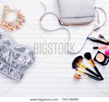 Woman's clothing and accessories placed on a wooden background. Top view fashion blogger's elegant accessories and makeup cosmetics