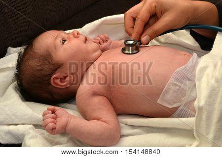 Midwife checks a newborn baby heart beat.