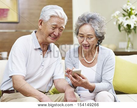 happy senior asian couple looking at mobile phone at home happy and smiling