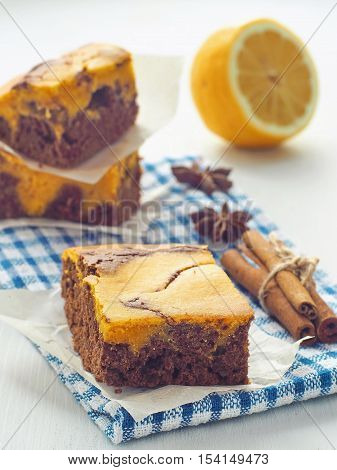 Piece of freshly baked brownie. Thanksgiving treat. Marble chocolate brownies with pumpkin. Selective focus on the front.