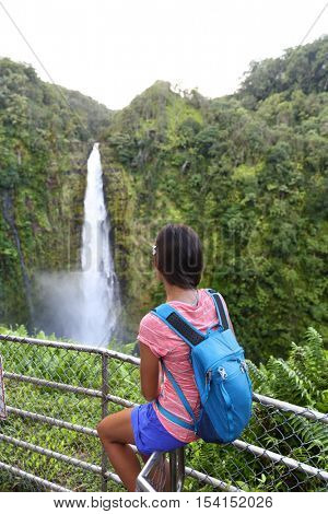 Hawaii travel tourist woman at scenic lookout viewpoint looking at Akaka falls, Big Island, Hawaii. Female hiker looking at a popular touristic hawaiian attraction beautiful waterfall.