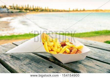 Traditional australian calamari rings with chips take away on the table at Port Elliot beach South Australia. Color toning applied