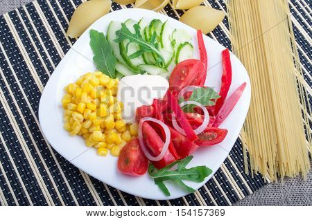 White Plate With Slices Of Fresh Tomatoes, Cucumber, Corn, Ruccola And Onion