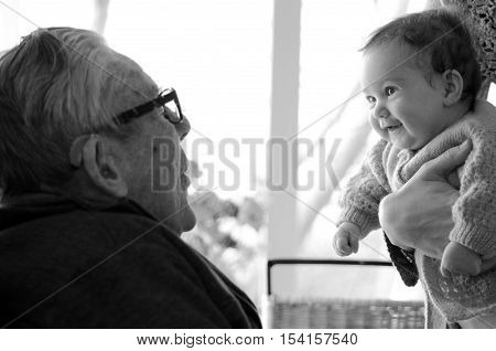 Great Granddad play with his great grandchild during home visit. Concept photo of senior citizen retirement pensioner relationship health and aging.