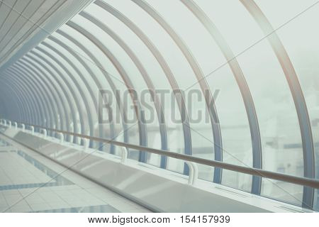 Teal and blue futuristic abstract glass and steal tunnel receding into the distance with regular beams and flare vintage color