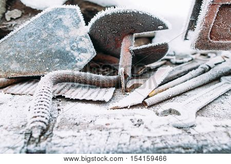 Ice boer outside with snow frost on it. Left outside tools in winter. Cold, early frosts, hoar concept