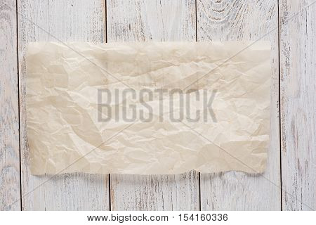 Cooking paper over wooden table background close up