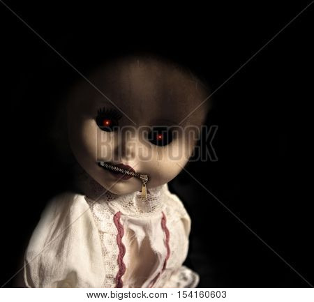 Vintage evil spooky doll with zipped mouth. On black background