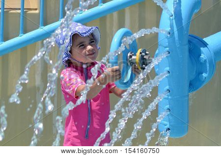 Child Play With Water Fountain In Water Park