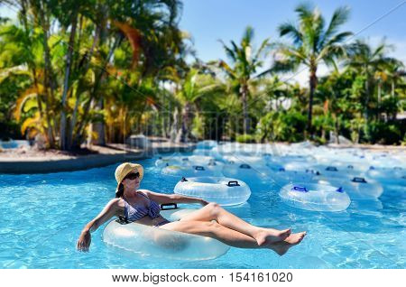 Sexy young woman float on inflatable tube relaxed at Water Park.