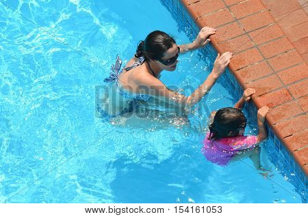 Young mother teach her child (girl age 04) to swim in a swimming pool.