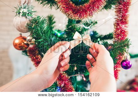 Hand hanging cute golden bow on Christmas tree. Pine-tree decorating for winter holidays celebration. Happy family, joy, new year concept