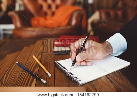 Close-up of hand with pen writing in notebook. Personal and business correspondence, writing letters, exchanging information, communication concept